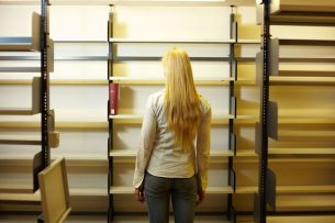 5934882 - student looking at empty book shelves in library